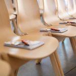 Leere Stühle mit Block und Stift im Seminarraum