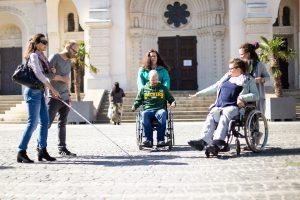 Hier sehen Sie ein Foto. Darauf befinden sich 6 Menschen mit und ohne Behinderungen auf einem öffentlichen Platz. 2 Personen sind Rollstuhlfahrer*innen. 1 Person hat verdeckte Augen und tastet mit einem Langstock, dabei wird sie von einer sehenden Person geführt.