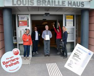 Das Foto wurde vor dem Louis Braille Haus aufgenommen. In diesem befindet sich der Blinden- und Sehbehindertenverband Wien, Niederösterreich und Burgenland. Am Foto sind 5 Personen zu sehen. Eine der Personen ist der Obmann Kurt Prall. Er hält das Zertifikat von Fair für Alle in den Händen.